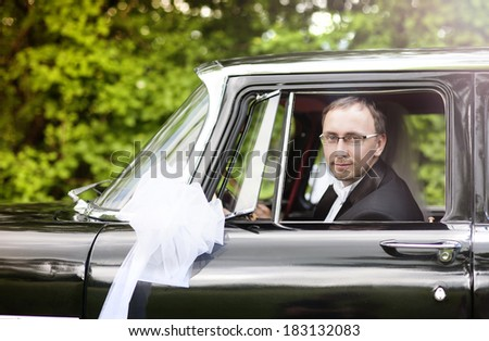 Happy young groom looking out of the retro car