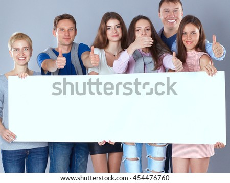 Happy young group of people standing together and holding a blank  - stock photo