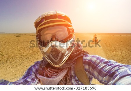 Happy young guy take selfie during desert excursion by quad - Man in helmet and adventure clothes make photo during vacation in exotic scenarios - Concept of activity holiday, freedom and adventure - stock photo