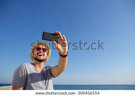 Happy young guy taking selfie with mobile phone while on vacation at the sea