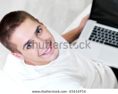happy young guy using laptop and lying on the sofa - high angle