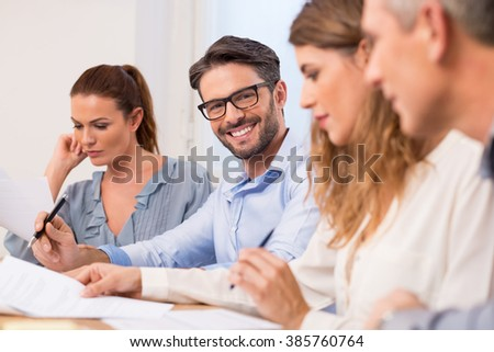 Happy young handsome businessman in a meeting wearing eyeglasses. Successful businessman writing important information in conference. Portrait of business man smiling during a business meeting. - stock photo