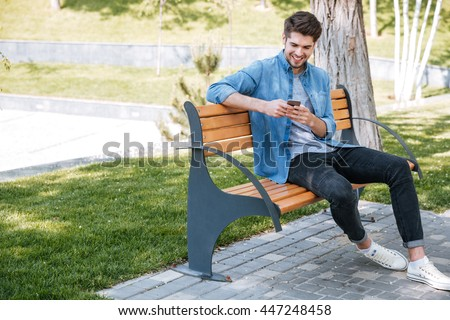 Happy young handsome man sitting on the bench outdoors and using smartphone - stock photo