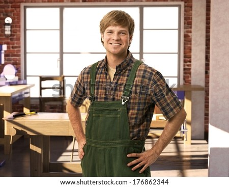 Happy young handyman carpenter in workshop, smiling. - stock photo