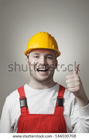 Happy young handyman with yellow hard hat - stock photo