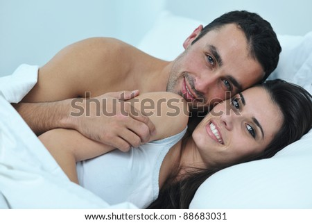 happy young healthy people  couple have good time in their bedroom make love and sleep - stock photo