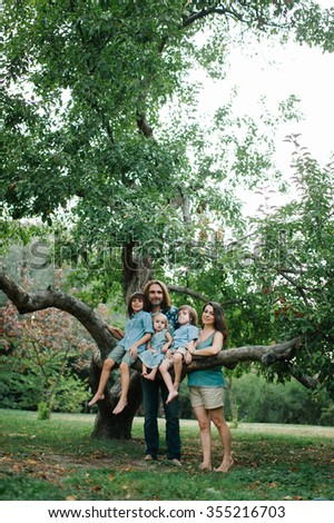 Happy young hipster family and their children posing on the tree in park on summer sunset