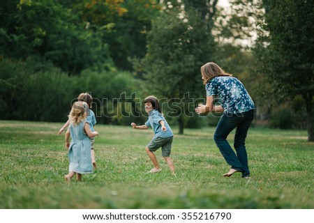 Happy young hipster family having fun while running, bowl,  rising up, piggyback ride their children in park on summer sunset  - stock photo