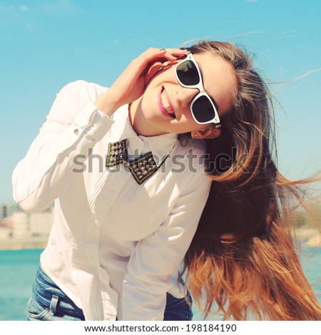 Happy young hipster girl in sunglasses walking on the beach in the summer. Outdoors, lifestyle. Shot retro colors. Photo toned style instagram filters - stock photo