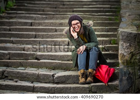 Happy young hipster woman is sitting on the outdoor stairs in old town, talking on mobile phone and smiling
