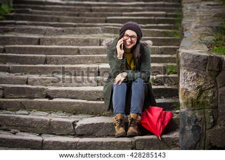Happy young hipster woman is sitting on the outdoors stairs, smiling and talking on the mobile phone.
