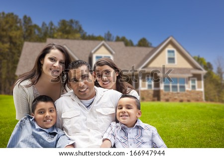 Happy Young Hispanic Family in Front of Their New Home.