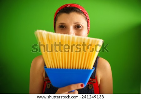 Happy young hispanic woman at home, doing chores and housekeeping, smiling at camera behind yellow broom - stock photo