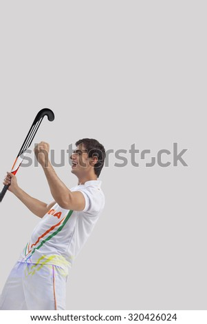 Happy young hockey player celebrating victory isolated over gray background