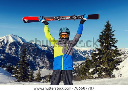 Happy young holding skis up in front of a mountain landscape