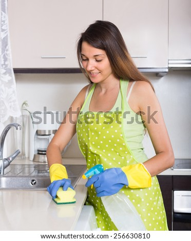 Happy young housewife cleaning furniture in kitchen at home
