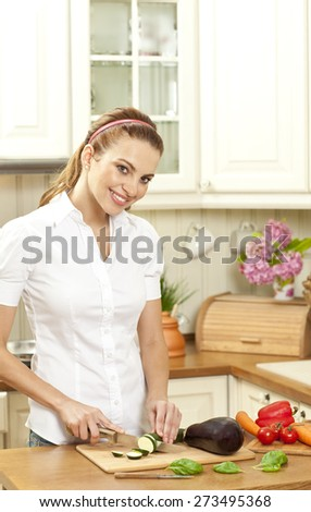 Happy young housewife cutting fresh vegetable in kitchen