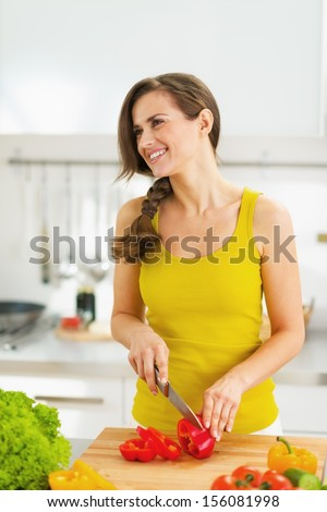 Happy young housewife cutting fresh vegetable salad
