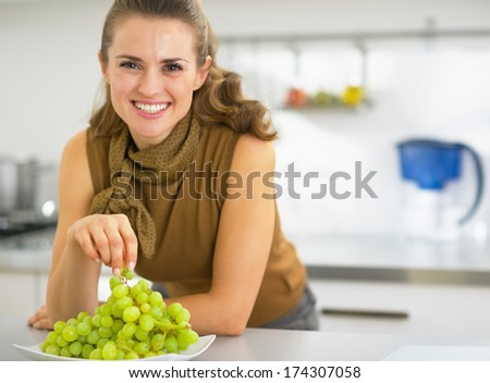 Happy young housewife eating grape - stock photo