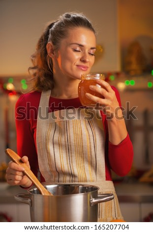 Happy young housewife enjoying fresh orange jam in kitchen