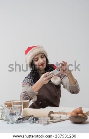 Happy young housewife making christmas cookies in kitchen and taking pictures on smartphone