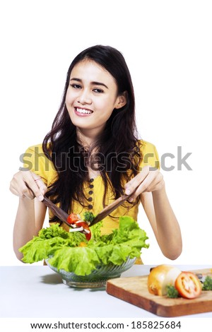 Happy young housewife mixing vegetable salad isolated on white
