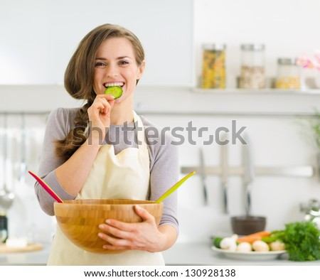 Happy young housewife tasting slice of cucumber from vegetable salad - stock photo