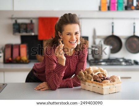 Happy young housewife with basket with mushrooms in kitchen - stock photo