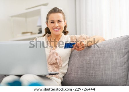 Happy young housewife with credit card making online shopping - stock photo