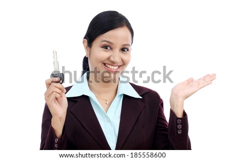 Happy young Indian business woman holding key against white background