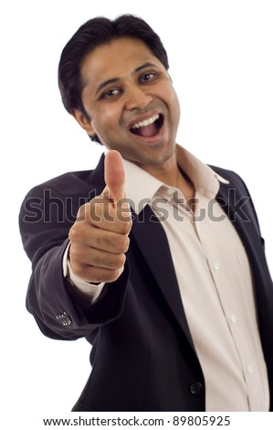 Happy young Indian businessman showing thumbs up sign isolated over white background - stock photo