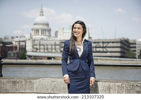Happy young Indian businesswoman with St. Paul's Cathedral in background - stock photo