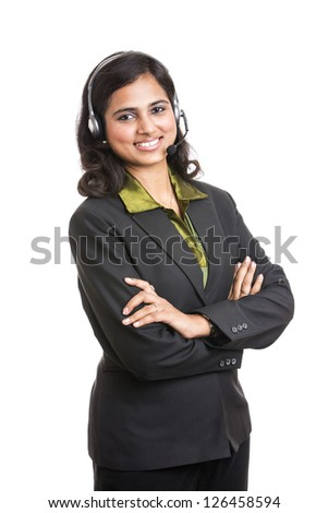 Happy young Indian call centre employee smiling with a headset over white - stock photo