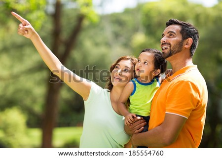 happy young indian family bird watching outdoors - stock photo