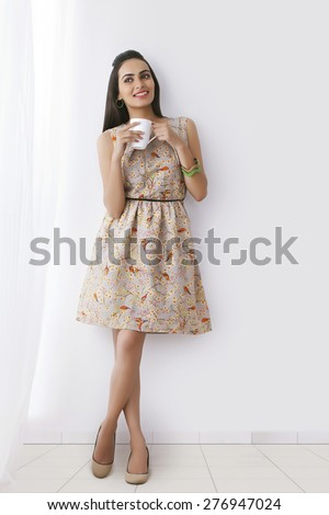 Happy young Indian woman having coffee while standing against white wall - stock photo