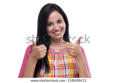 Happy young Indian woman wearing kitchen apron and showing thumbs up