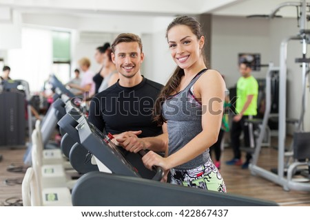 Happy young instructor talking to a woman who is on treadmill.