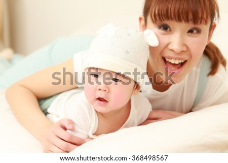 happy young Japanese mom and her baby