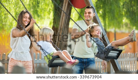 Happy young joyful family of four at playground's swings. Focus on woman