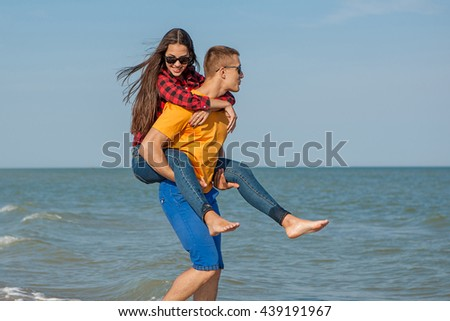 Happy young joyful guy and girl having fun on the beach, laughing together. During summer holidays vacation on sea. Beautiful energetic couple friends adolescents.