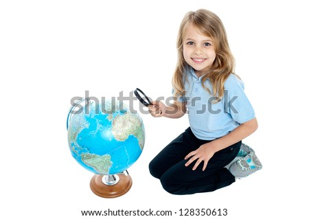 Happy young kid with magnifying glass kneeling on the floor, globe placed in front of her.