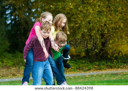 Happy young kids giving each other piggy back rides.  Playing and having fun actively outside. - stock photo