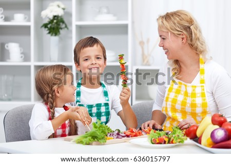 Happy young kids preparing a healthy snack with their mother - having fun in the kitchen