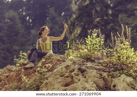 Happy young lady enjoying the nature while resting in the sunlight on top of a rock during a hike. - stock photo