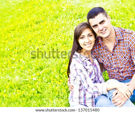 Happy young latin hispanic couple embracing outdoor on spring green grass background - stock photo