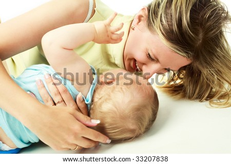happy young laughing mother with her baby on the floor - stock photo