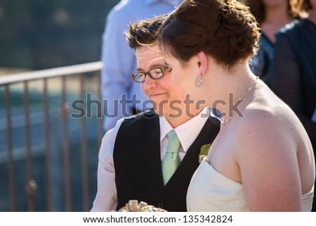 Happy young lesbian married couple standing outside - stock photo