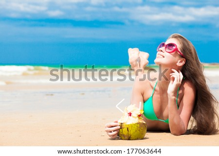 Happy young  long haired woman in bikini with coconut lying on the beach - stock photo