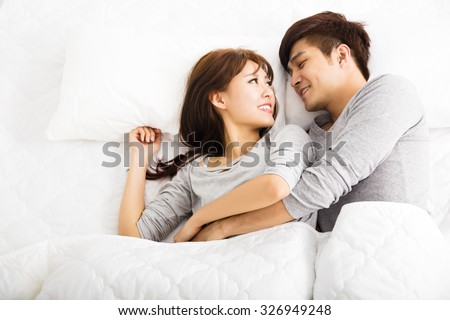 happy young lovely couple lying in a bed - stock photo
