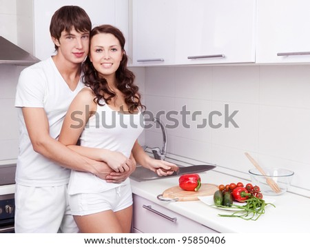 happy young loving couple cooking together in the kitchen at home - stock photo